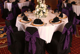 black chaircovers with black sashes and black napkins