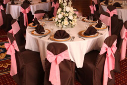 chocolate chaircovers with pink sashes and chocolate napkins