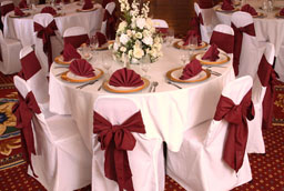 white chaircovers with burgundy sashes and burgundy napkins